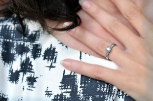 Close-up image of an engagement ring on a woman's hand held against her neck. ** Note: Slight graininess, best at smaller sizes